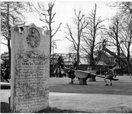 View of children's playground at St John's Wood Churchyard, with the gravestone of Samuel Godley in the foreground, 1955 | Copyright Westminster City Archives