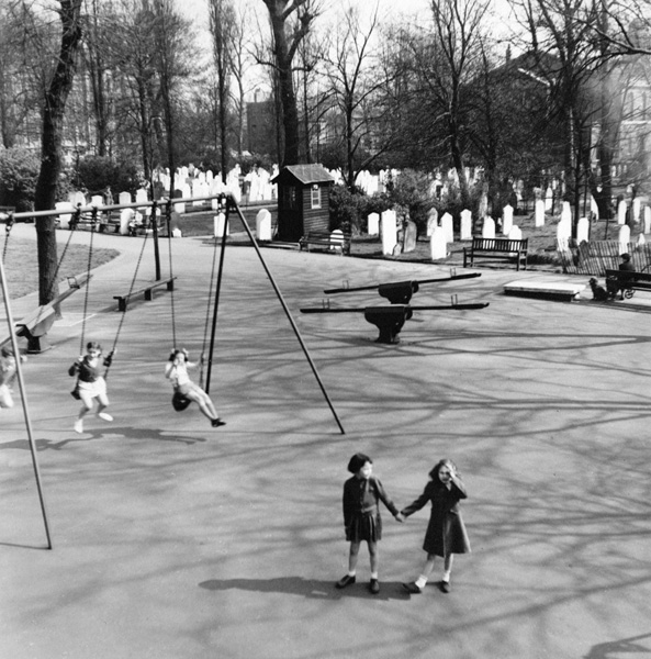 View of children's playground at St John's Wood Churchyard in 1951. The girl in the coat is now Mrs Chapman and she is with her friend Glenda. They lived in Winchelsea House, on the corner of Lisson Grove and St Johns Wood Road. Photograph by by H Doeling | Copyright Westminster City Archives
