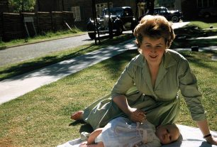 My niece (in hand knitted matinee jacket) with me outside as the building starts across the road autumn 1959 | Bridget Clarke