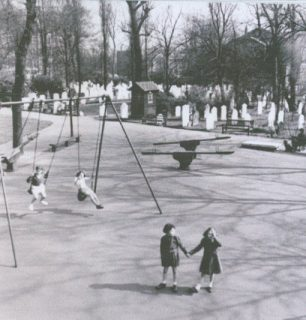 Playground in 1951. The girl in the coat is now Mrs Chapman and she is with her friend Glenda.  They lived in Winchelsea House, on the corner of Lisson Grove and St John's Wood Road. | Westminster City Archives photograph by H Doeling.